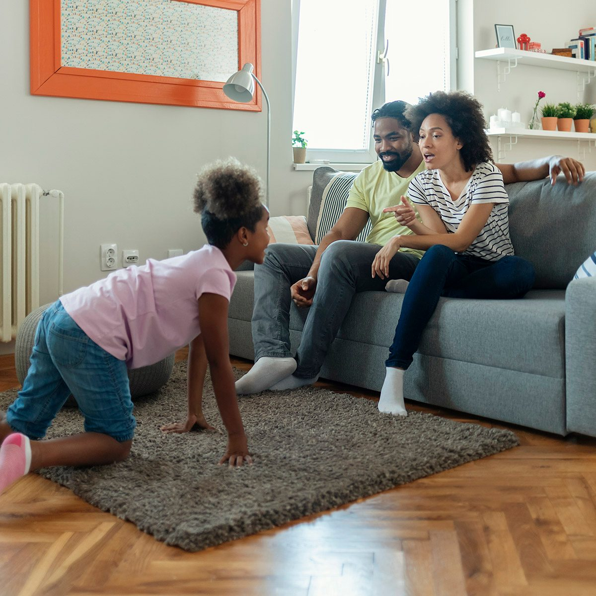 Young Parents and Their Daughter Are Having Fun and Playing Charades Together. Portrait of Happy Family Having Fun at Leisure. Entertainment Concept.