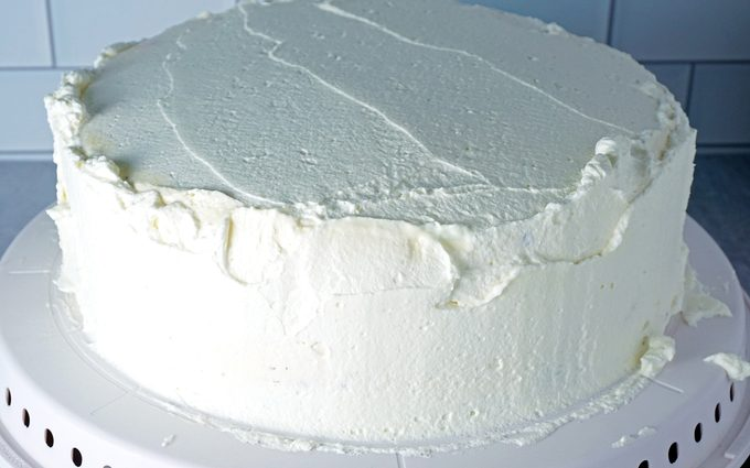 spreading a thin layer of whipped cream frosting onto ice cream cake