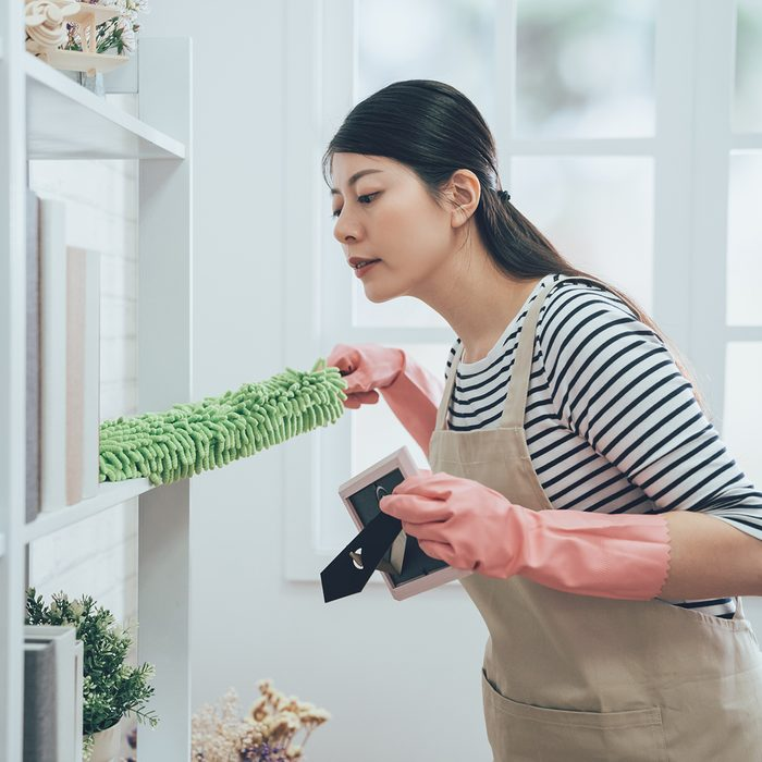 asian housekeeper in apron dusting the bookshelf by feather duster taking up the picture frame carefully cleaning in living room at home. young wife in rubber gloves doing housework.