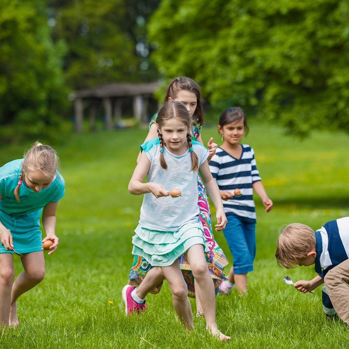 Group of children competing in an egg-and-spoon race in a park, Munich, Bavaria, Germany