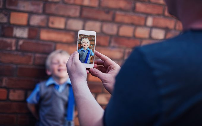 Father at taking a photo of his son.