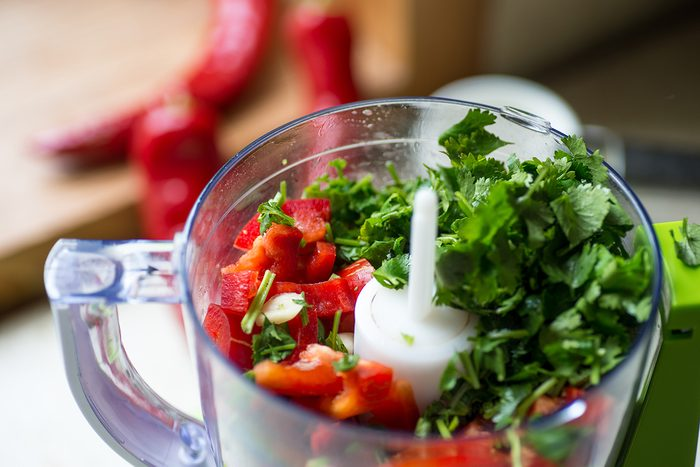 Blender with fresh bell pepper and cilantro on and kitchen table.