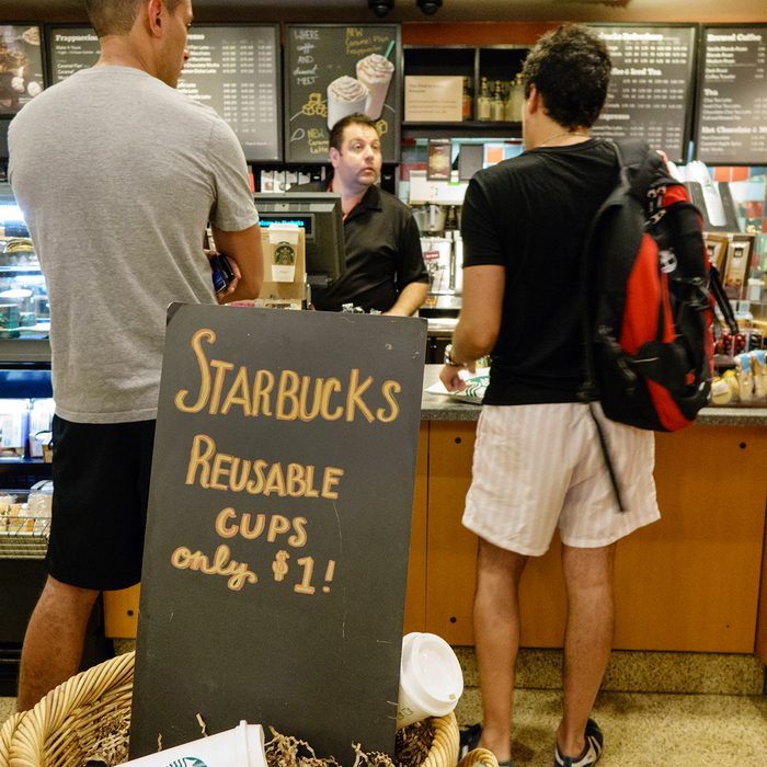 Interior of Starbucks Coffee with customers standing at the counter behind reusable cups sign. (Photo by: Jeffrey Greenberg/Universal Images Group via Getty Images)