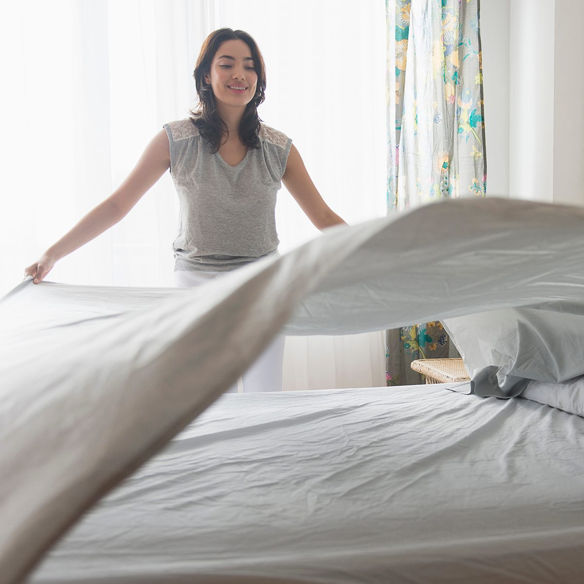 Young woman spreading sheet on bed