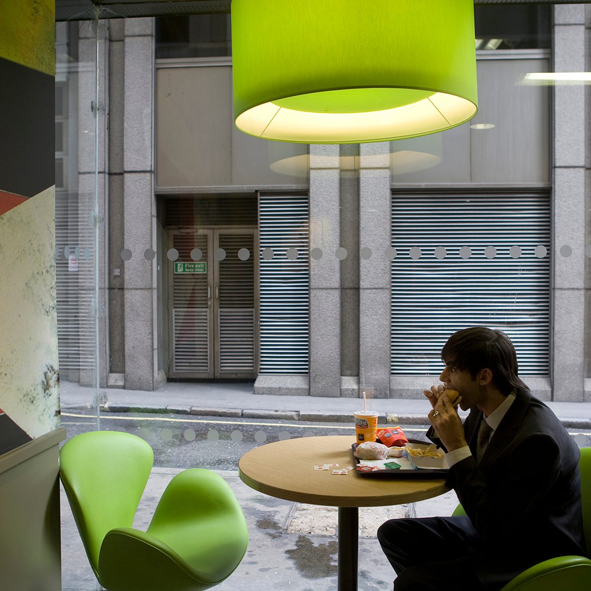 A McDonald's customer tucks into his Big Mac, oblivious to the new trendy coffee bar style ambience and design at the Cannon Street branch of McDonalds in the City of London. This is one of the flagship branches for this new design as the corporation takes on the process of 're-imaging' the fast food chain. This redesign, with new colours: khaki, lime, orange and russet, in a vibrant mixture of geometrics, lines and swooshes has been created for McDonald's by French Designer, Philippe Avanzi. It includes comfortable easy-chairs and stools, drop down lighting and in total, a whole new feel. This is part of a new global strategy to give McDonalds branches in different countries a uniquely local character, both in terms of the decor and some of the food served. The menu has even seen the introduction of sustainably grown coffee, organic milk etc. (Photo by Gideon Mendel/Corbis via Getty Images)