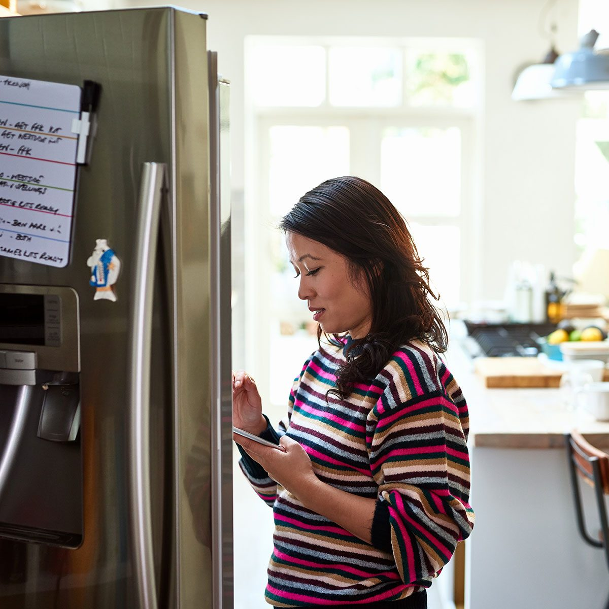 Mid adult woman checking food in fridge holding tablet