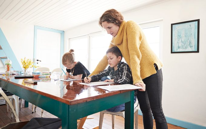 Mother homeschooling daughter and son at dining table