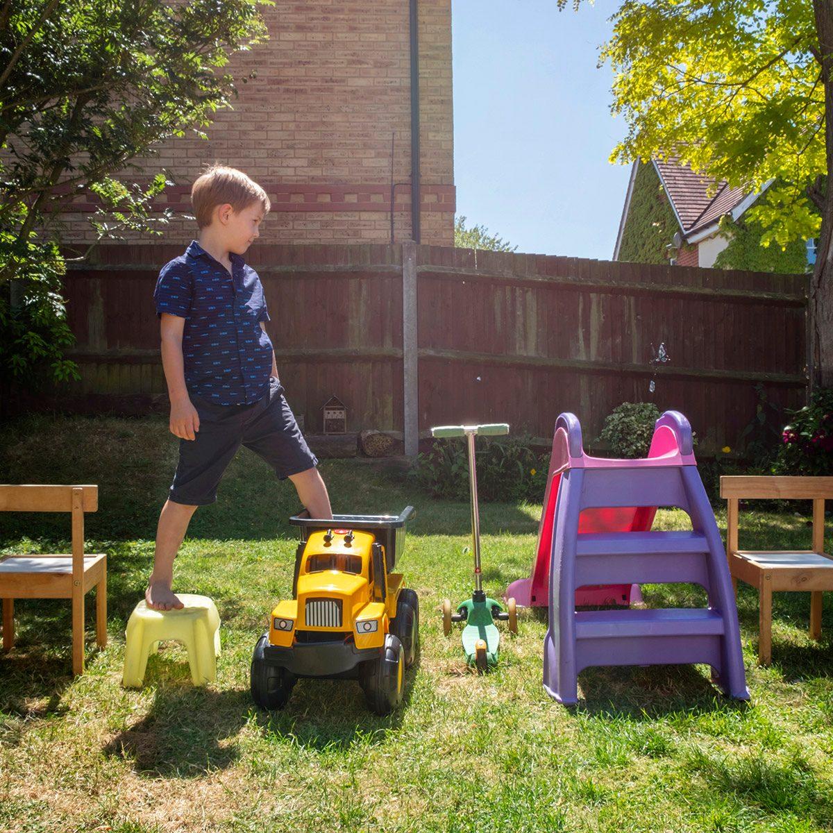 Boy walking on toys arranged in yard
