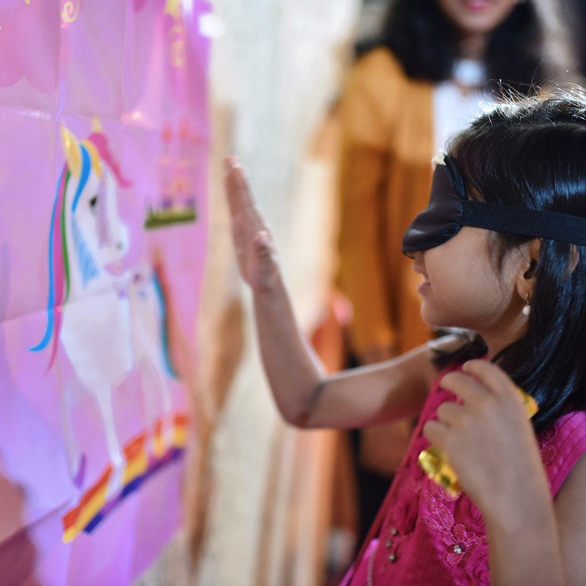 blindfolded girl pinning horn to Unicorn