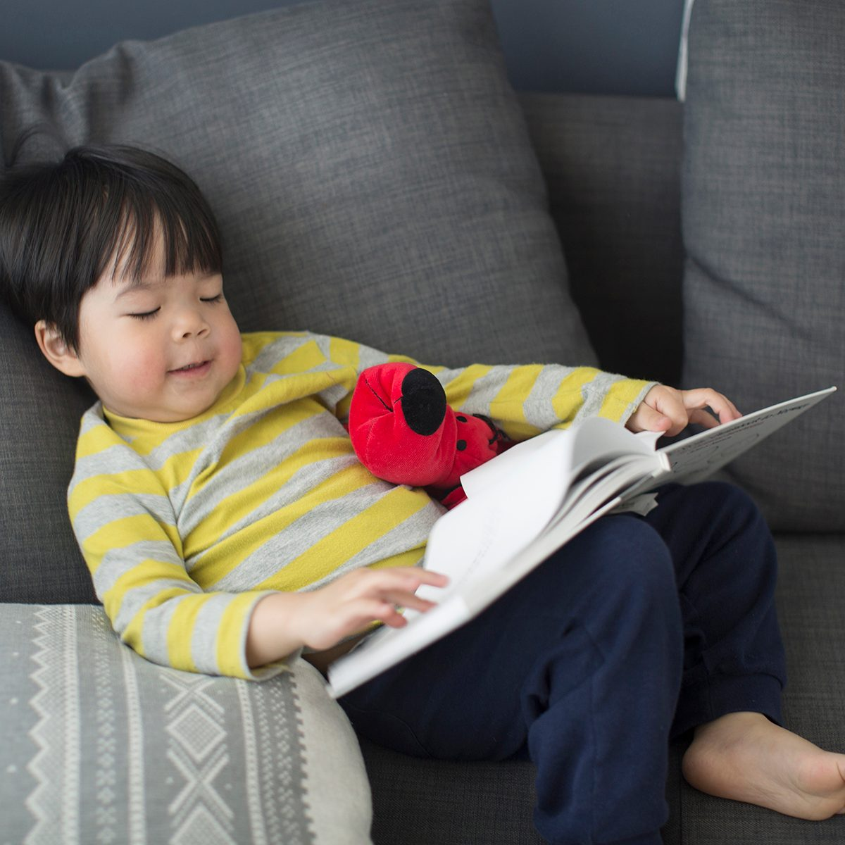 Asian toddler boy relaxing, reading on sofa.