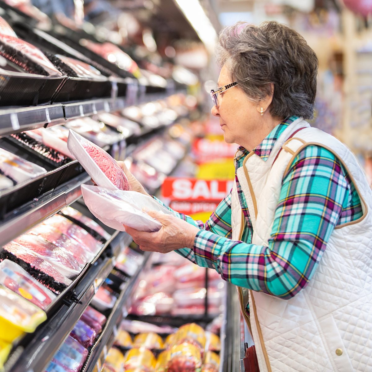 Senior woman comparing prices for meat selection.