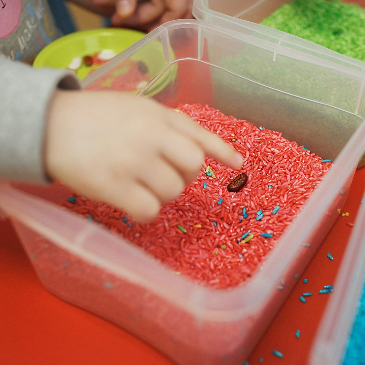 Children play educational games with a sensory bin in kindergarten.