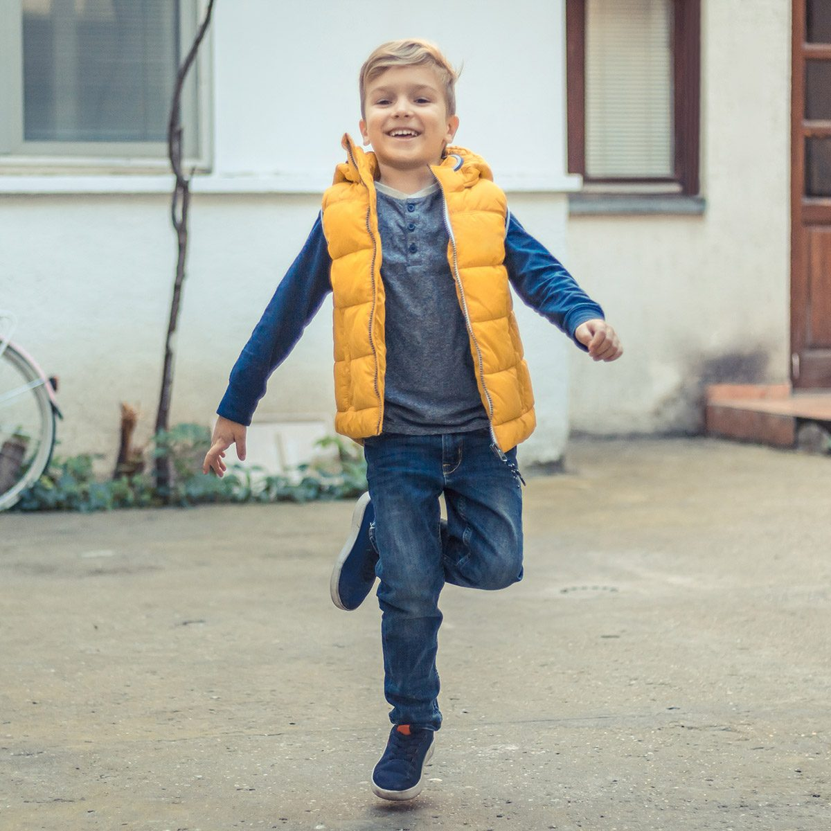 Happy kid having fun and jumping on one leg outdoors.
