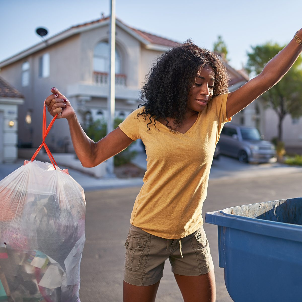 african american woman taking out the trash in las vegas neighborhood during the day
