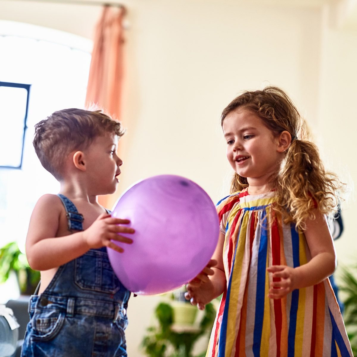 Young boy and girl having fun playing game with purple balloon at home, low angle, sharing, togetherness, friendship
