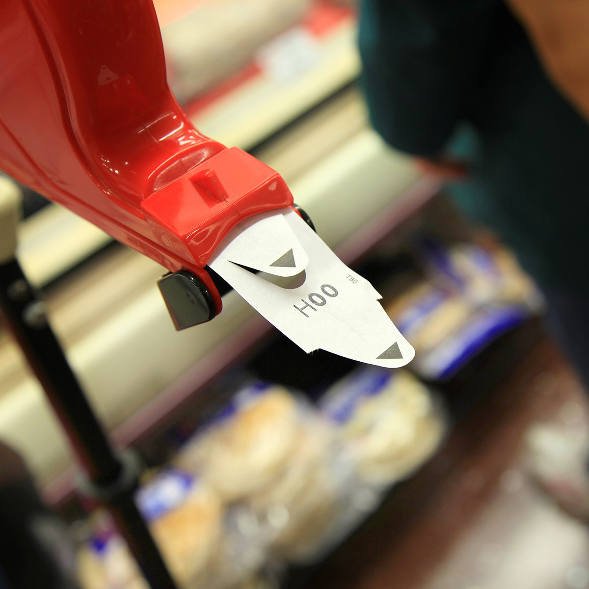 A customer is standing next to a ticket number dispenser at a grocery store, meat section.