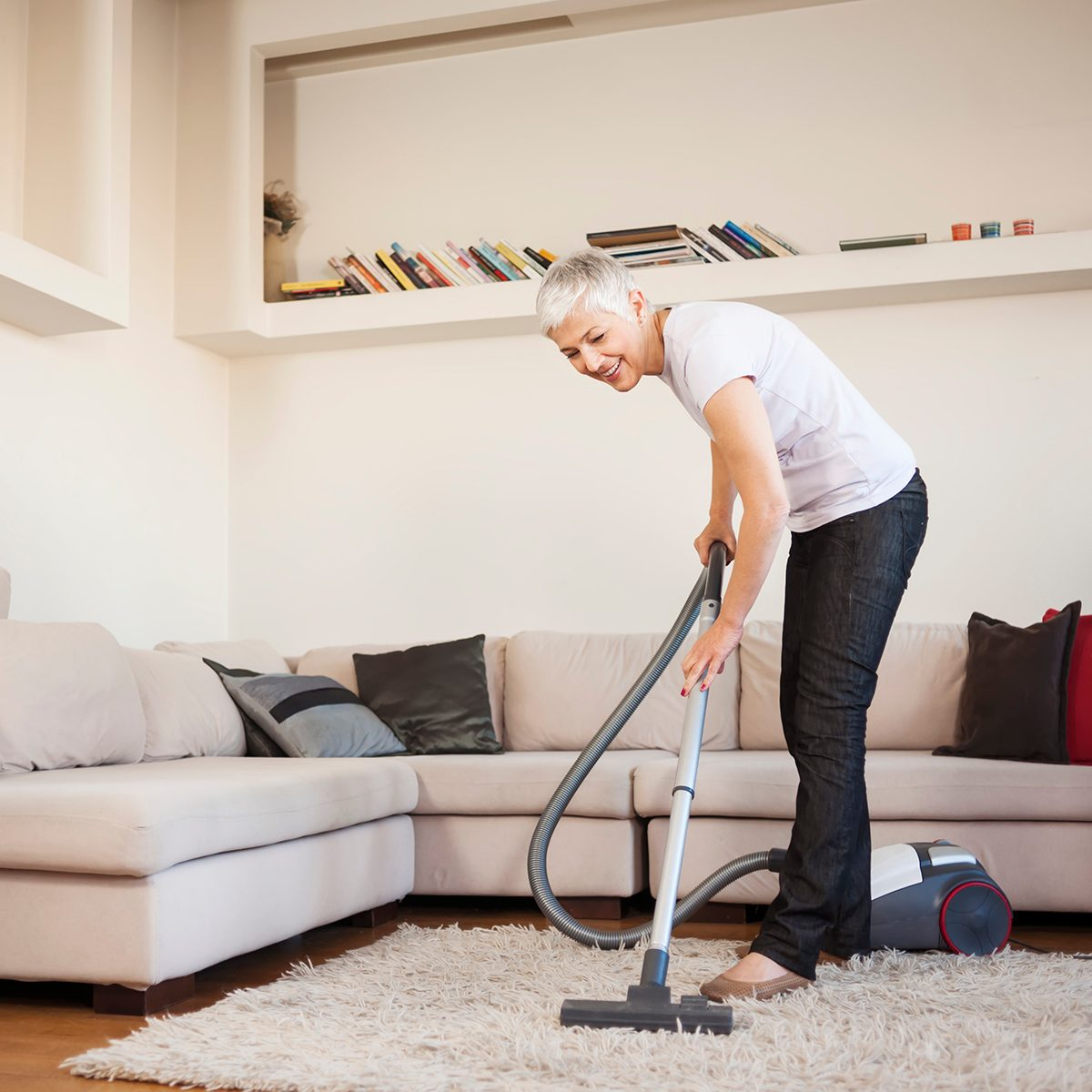 Woman cleaning carpet with a vacuum cleaner in room