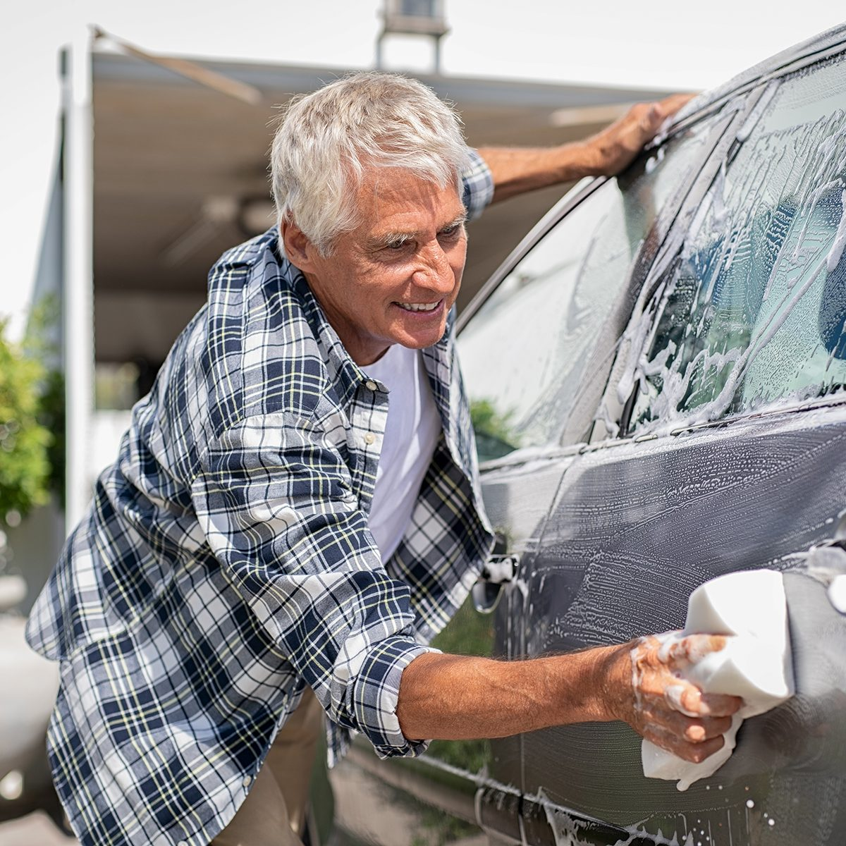 Happy senior man washing car with soap and foam. Old retired man cleaning automobile with sponge in a sunny day. Satisfied driver washing his gray car near the garage.