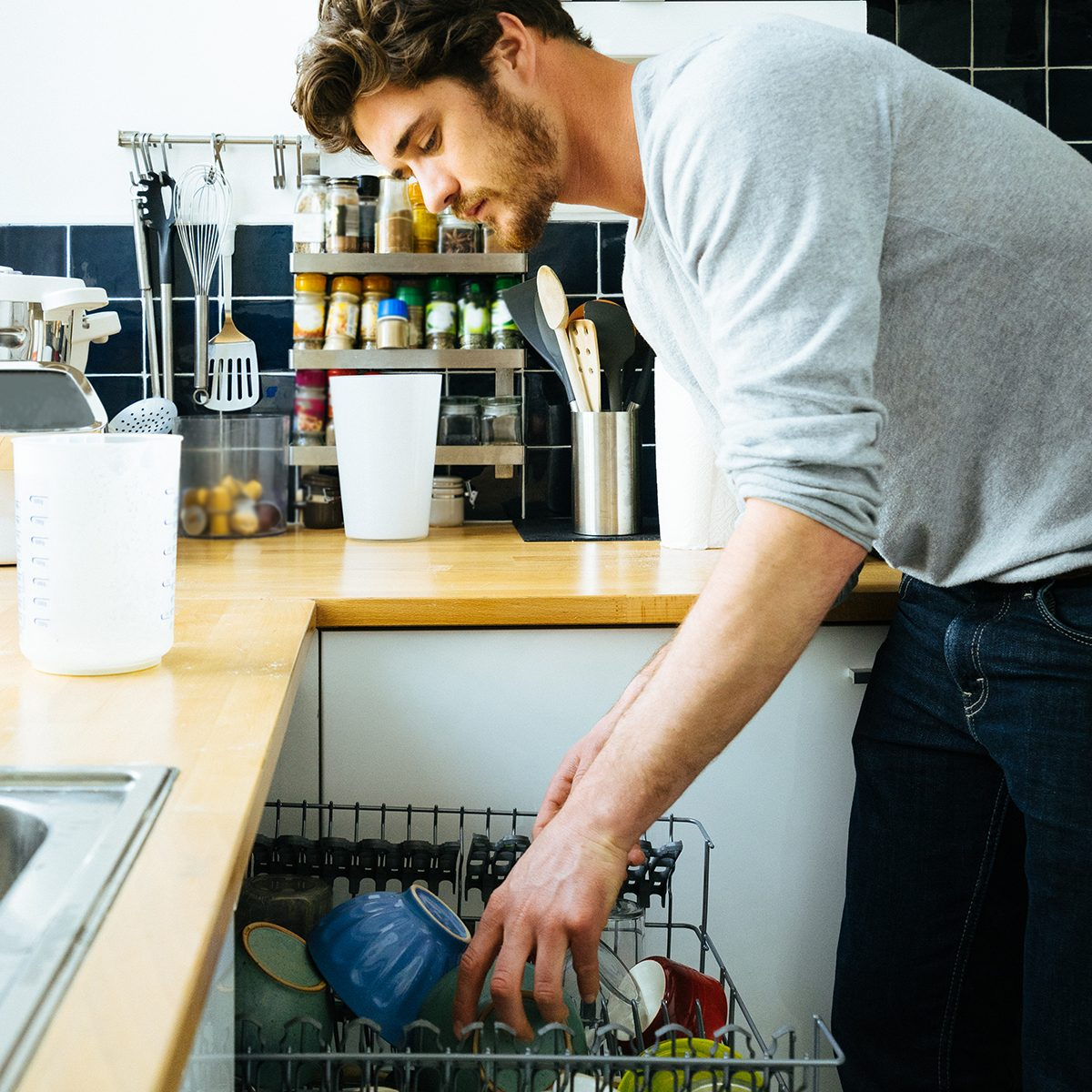 Man at home loading the dishwasher, putting dirty dishes into the machine.
