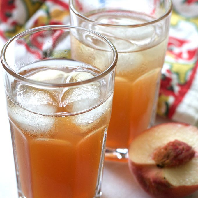 vertical photo of two glasses of white peach iced tea
