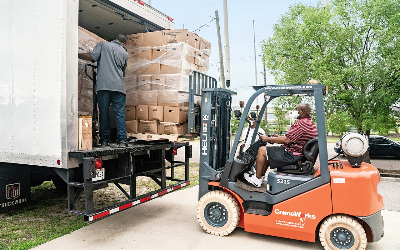 Eric using a forklift to gather donations onto a truck