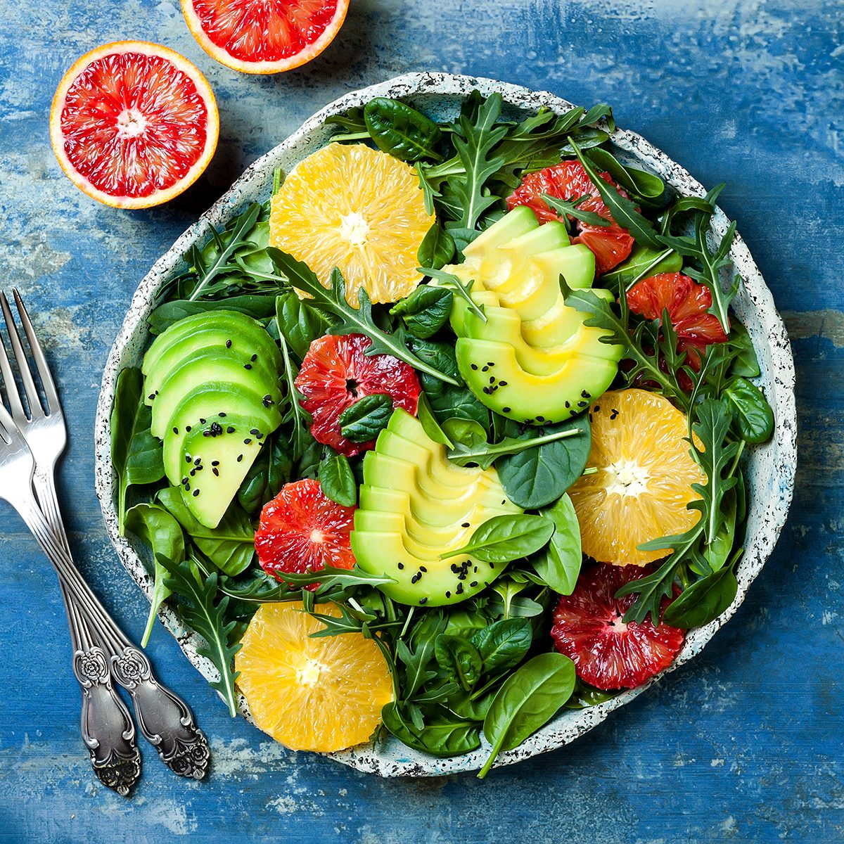 Citrus salad with mixed greens and blood orange. Vegan, vegetarian, clean eating, dieting, food concept. Blue stone background.