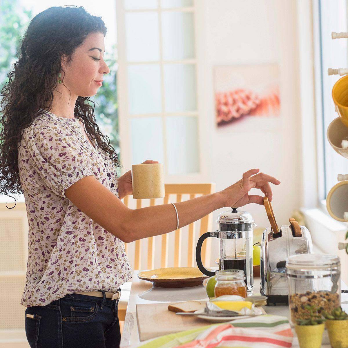 Mixed race woman preparing breakfast in kitchen