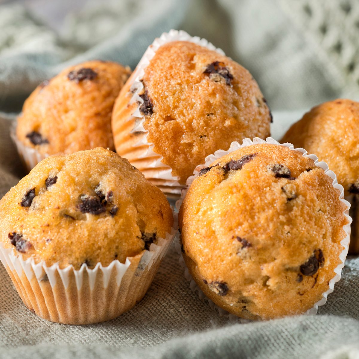 Several muffins with chocolate chips on a linen tablecloth at breakfast