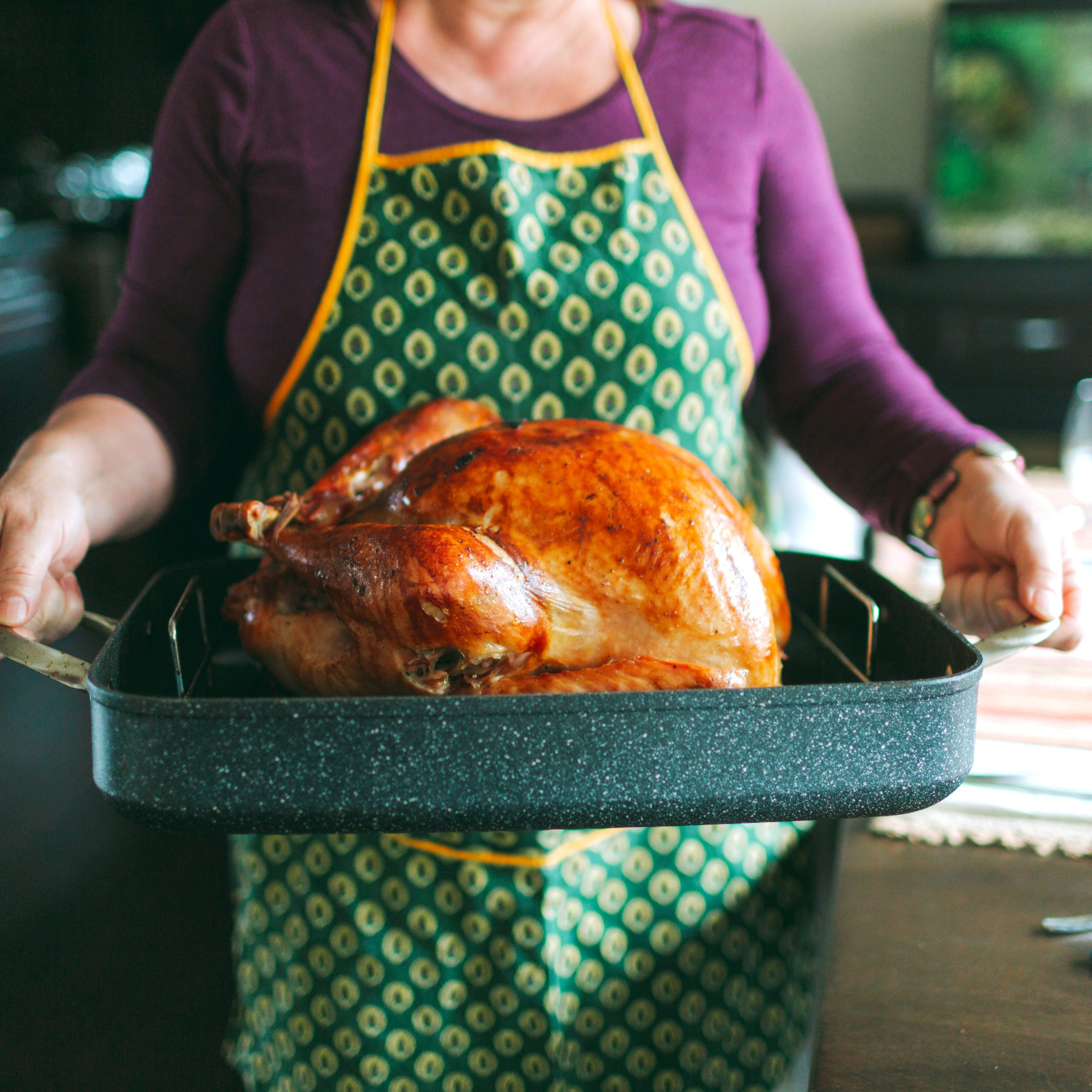 Midsection Of Woman Carrying Tray With Roast Turkey In Kitchen