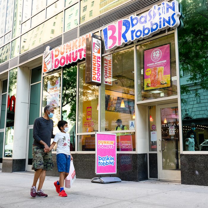 NEW YORK, NEW YORK - JULY 31: People wear protective face masks outside Dunkin' Donuts and Baskin-Robbins as the city continues Phase 4 of re-opening following restrictions imposed to slow the spread of coronavirus on July 31, 2020 in New York City. The fourth phase allows outdoor arts and entertainment, sporting events without fans and media production. (Photo by Noam Galai/Getty Images)