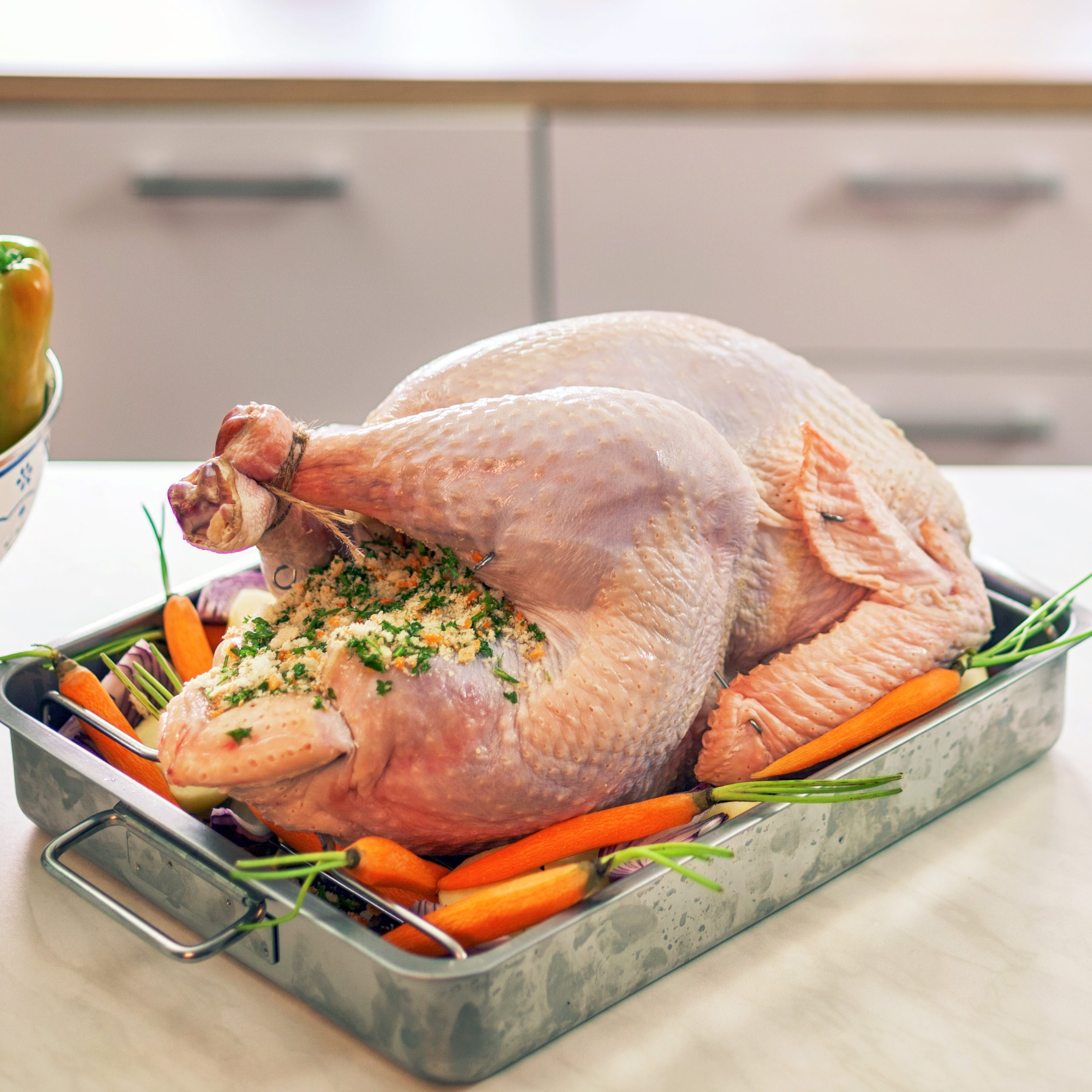 Raw turkey surrounded with side dishes in baking sheet ready to be prepared for Holidays