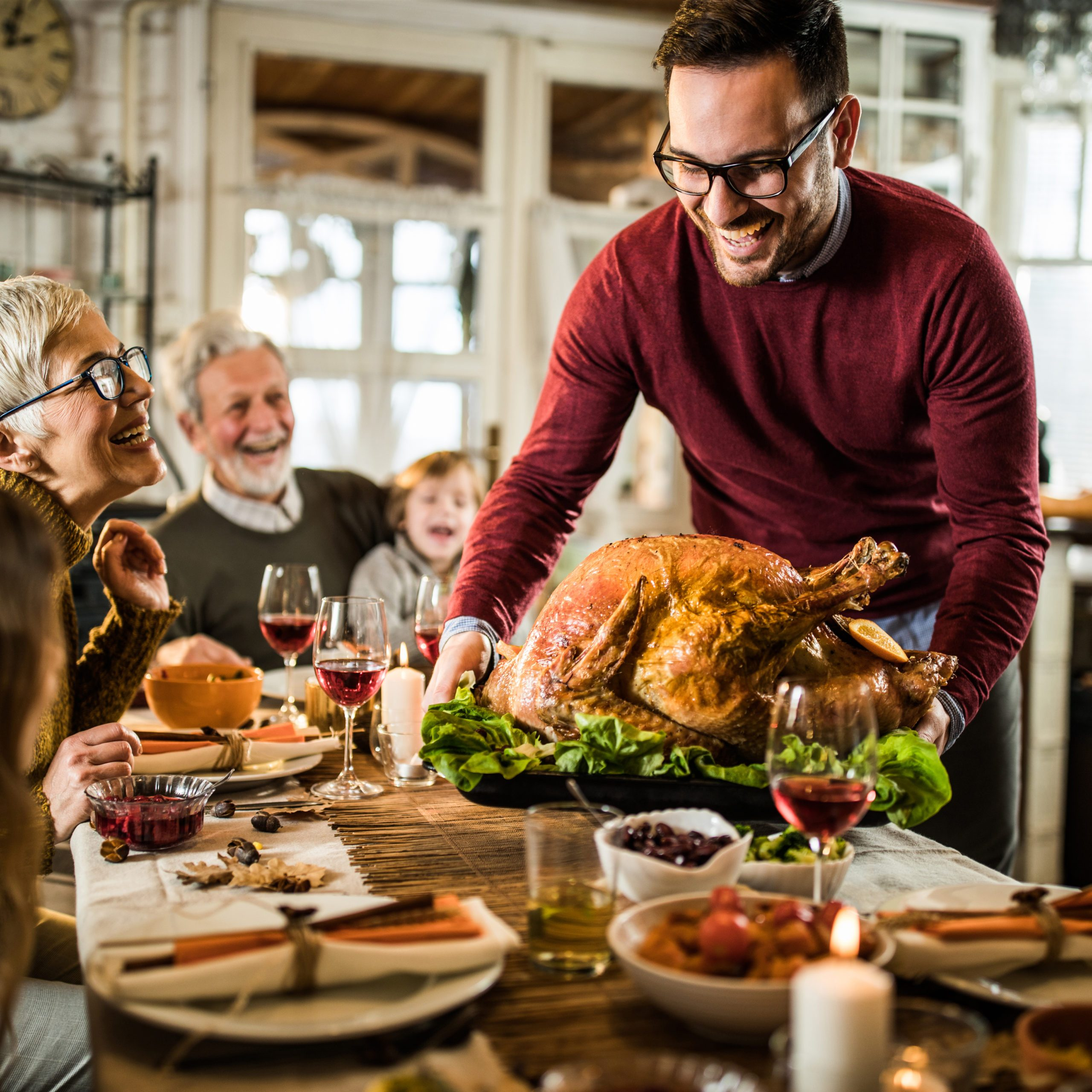 Happy man serving roasted turkey to his family during Thanksgiving dinner at dining table.