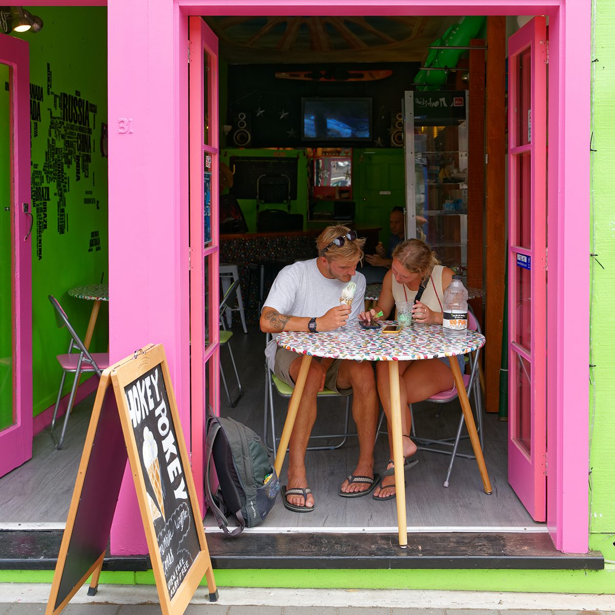 Picton, Marlborough Sounds/New Zealand - February 1, 2020: Tourists eating ice creams engrossed with their cellphones in an ice cream shop in Picton, Marlborough Sounds, New Zealand.