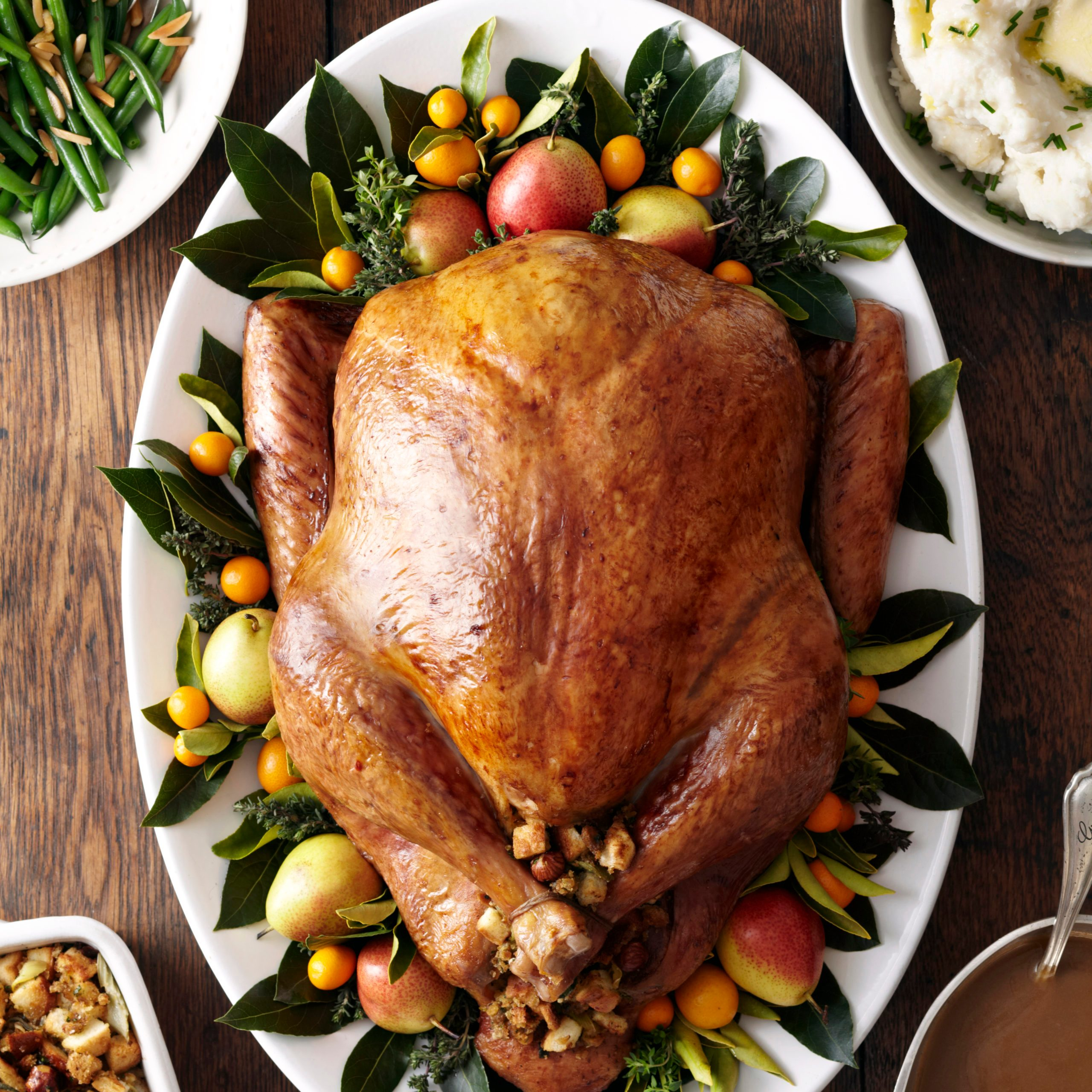 Turkey, stuffing, and gravy dishes on wood surface