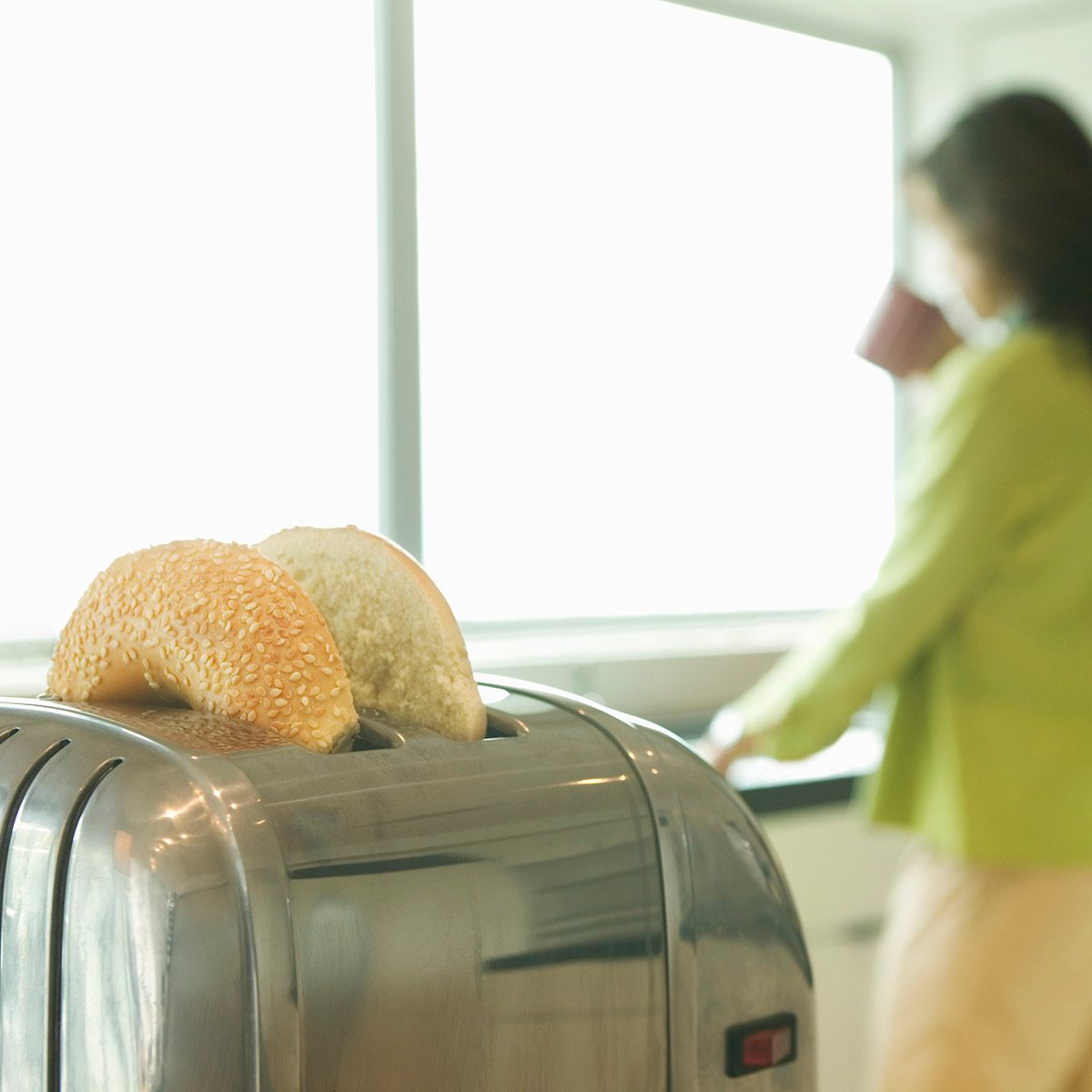 Woman in kitchen drinking coffee, bagels in toaster (focus on toaster)
