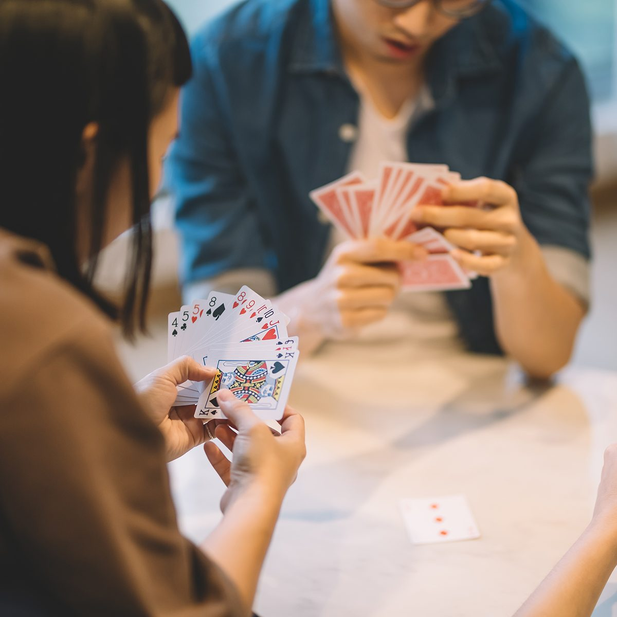 asian chinese friends playing poker cards game in living room