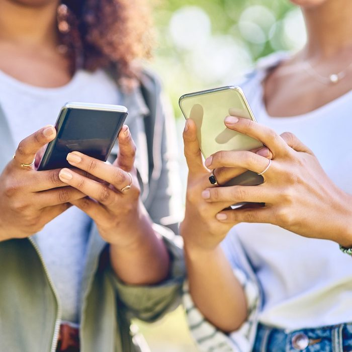 Cropped shot of unrecognizable women using cellphones outdoors