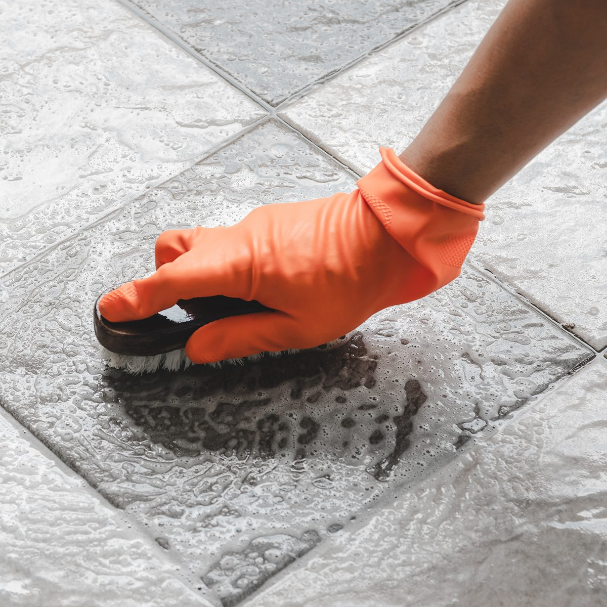 Hand of man wearing orange rubber gloves is used to convert scrub cleaning on the tile floor.