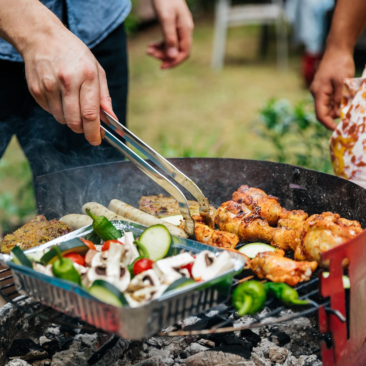 A close up of aman cooking different foods on a barbecue.