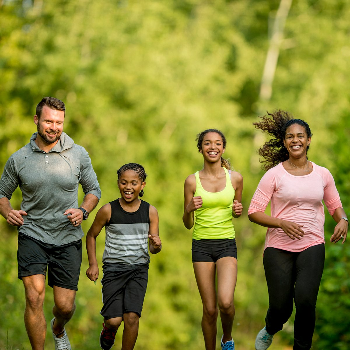 A multi-ethnic family (mother, father, son, daughter) getting exercise by going for a jog at the park.