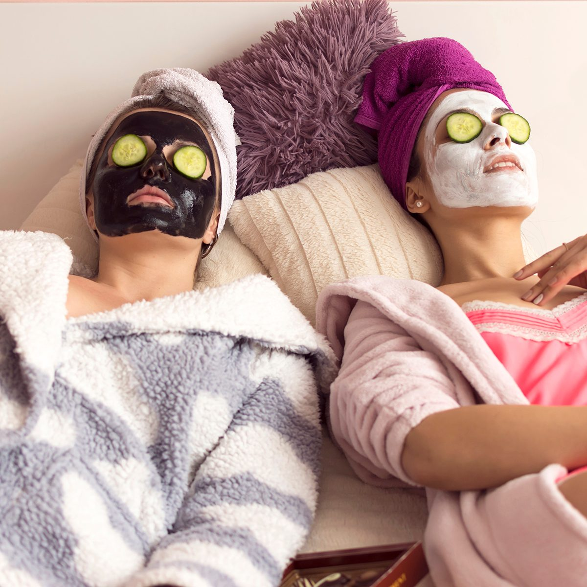 Two young girlfriends making facial mask at home