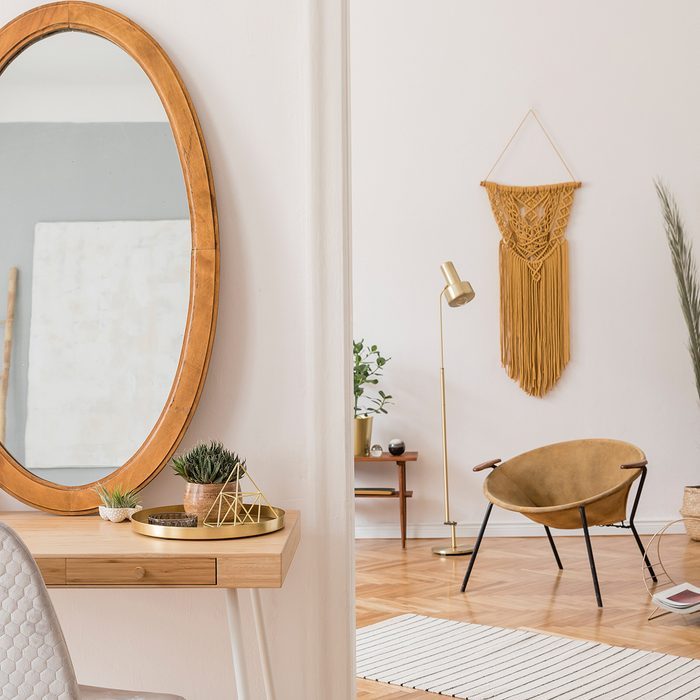 Off white room with mirror and a doorway into another room