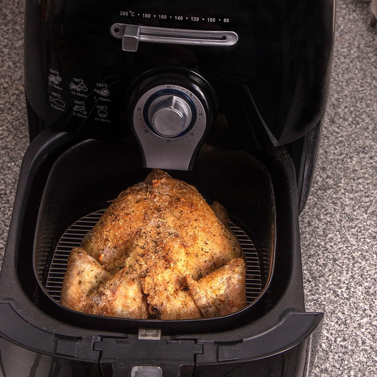 Roasted turkey in the hot air fryer / oven in the kitchen seen from above.