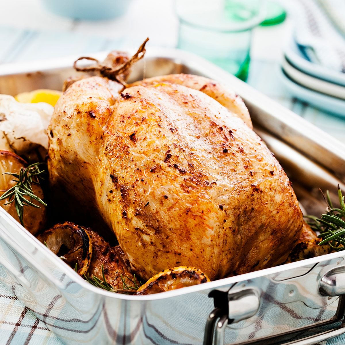 Roasted turkey in a pan with lemon, garlic and rosemary