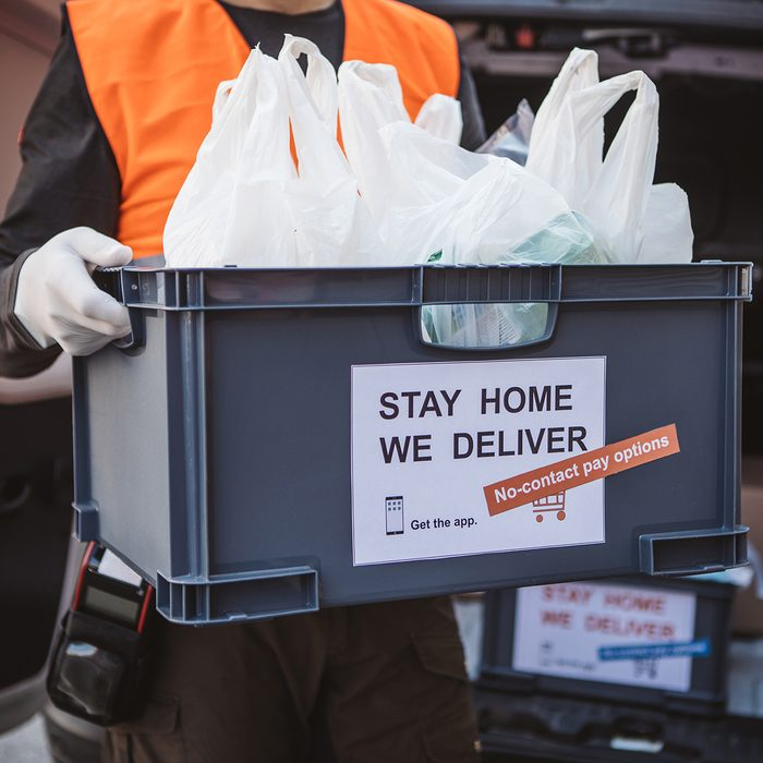 GROCERY SHOPPING  RE-IMAGINED Food Trends Report, Delivering food ordered online while in home isolation during quarantine. Stay home we deliver sign on box.