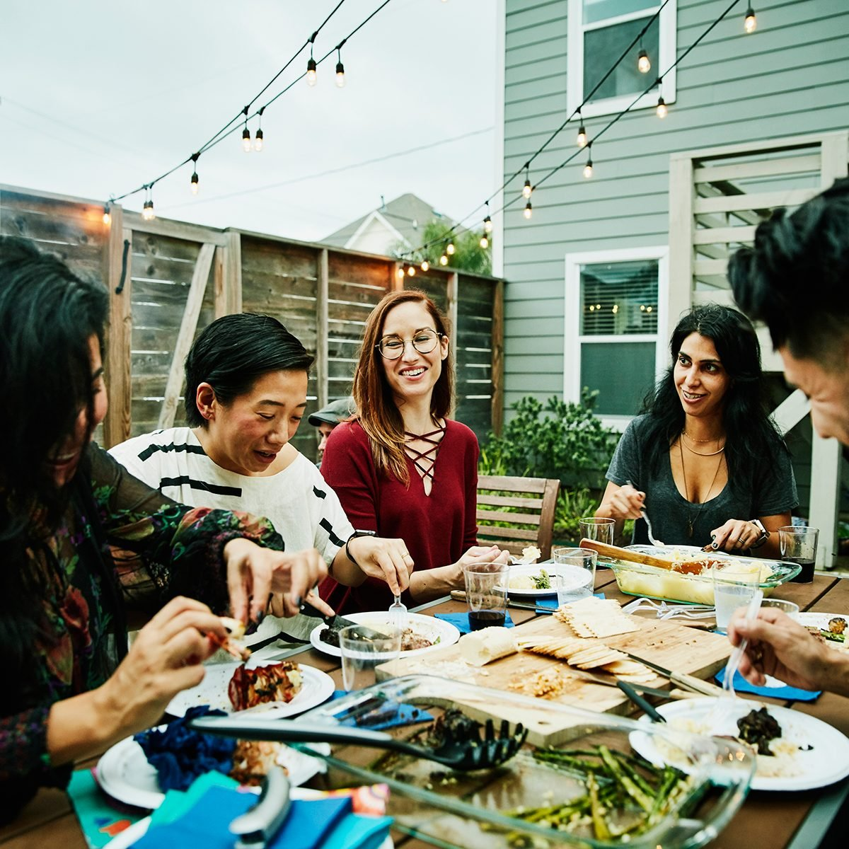 Smiling and laughing friends sharing dinner at table in backyard