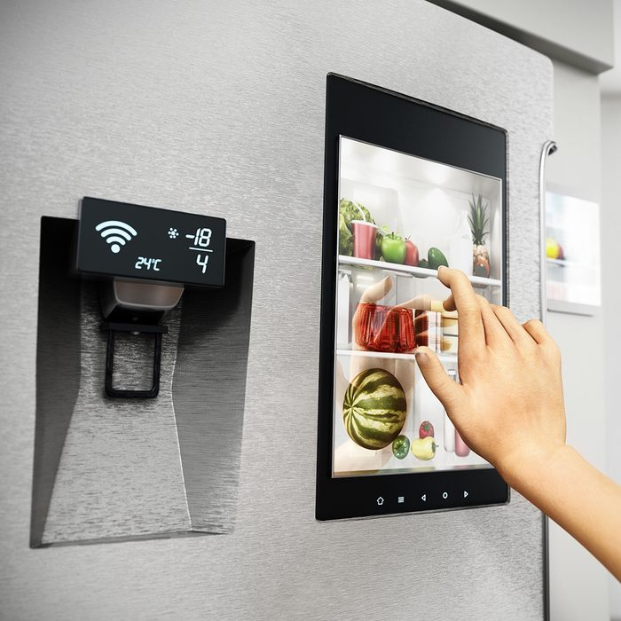 SMART KITCHENS  GET SMARTER Food Trends Report, Hand controls smart refrigerator interface with an image of the interior.