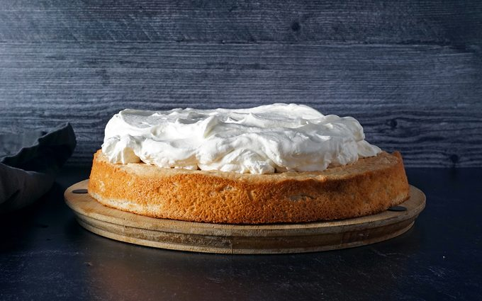 adding a thick layer of whipped cream for Swiss Pastry Shop black forest cake
