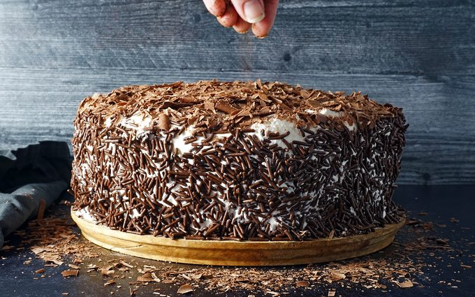 covering Swiss Pastry Shop Black Forest Cake generously with chocolate sprinkles and shavings