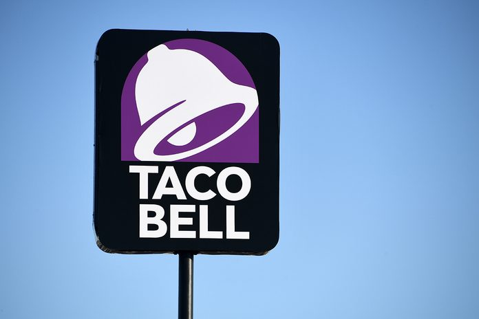 """LAS VEGAS, NEVADA - MARCH 30: An exterior view shows a sign at a Taco Bell restaurant on March 30, 2020 in Las Vegas, Nevada. Taco Bell Corp. announced that on March 31, 2020, the company will give everyone in the country one free beef nacho cheese Doritos Locos Taco, no purchase necessary, to drive-thru customers at participating locations while supplies last as a way of thanking people who are helping their communities in the wake of the coronavirus pandemic. The company also announced it would relaunch its Round Up program, which gives customers the option to """"round up"""" their order total to the nearest dollar, to raise funds for the No Kid Hungry campaign. The Taco Bell Foundation will also be donating $1 million dollars to the campaign. (Photo by Ethan Miller/Getty Images)"""